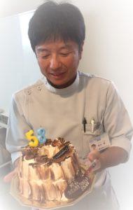 ケーキを持った院長の画像
